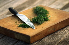 Herbs. Dill, knife and chopping board.