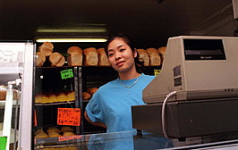 A vietnamese shop assistant working at the till in