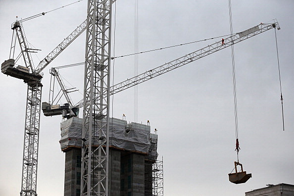 A Construction Worker Walks Out on the Jib of a Tower Crane