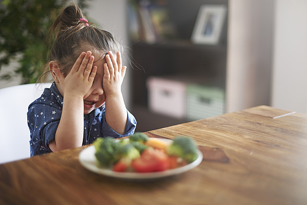 little girl angry about eating vegetables
