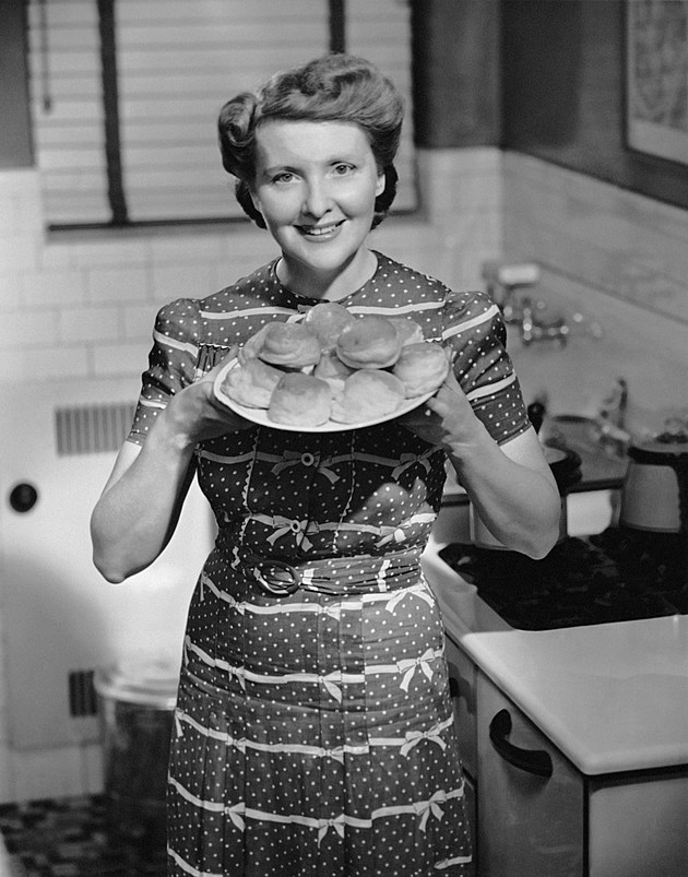 Woman holding out plate of biscuits